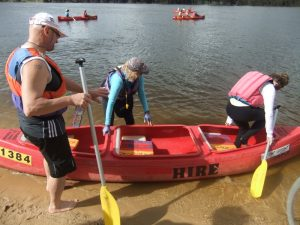 3 people getting into a canoe and 3 canoes already on the Swan River.