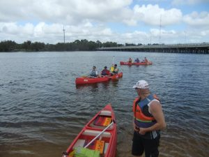 Two canoes with 3 people in them and 1 person about to get in a canoe on the Swan River