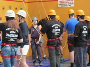 DB Camp 2014 members in harnesses holding ropes being instructed on how to Abseil